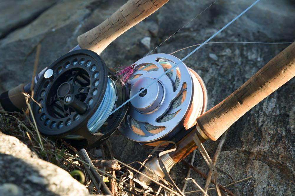 Two fly reels in grass by river