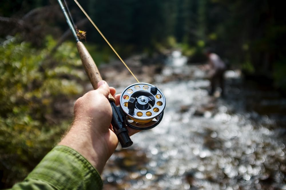 Fly Reel Held Out Over River