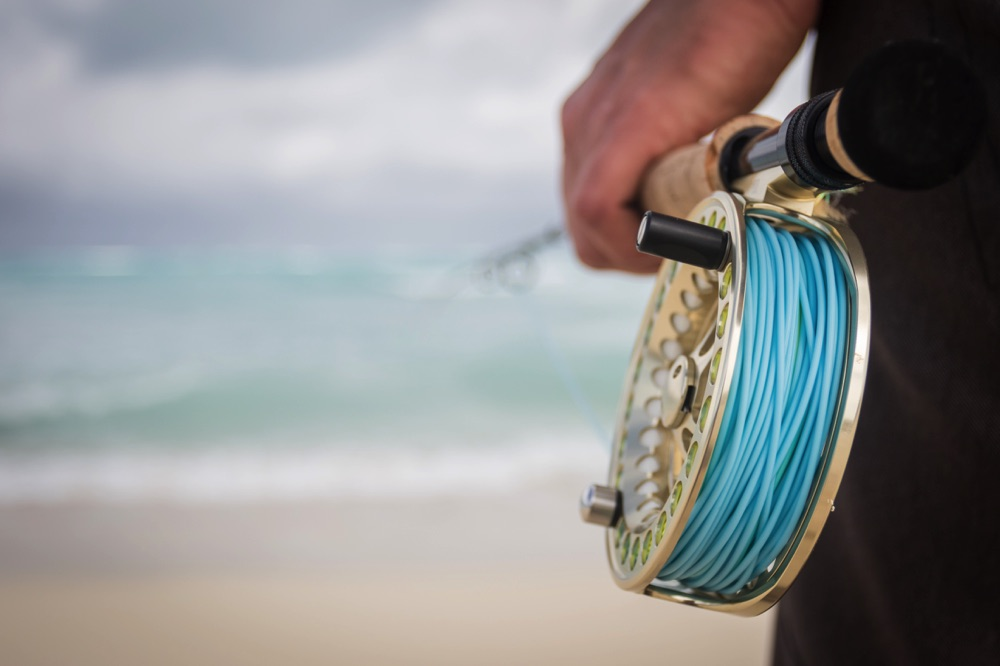 A fly rod on a beach with fly line on it.