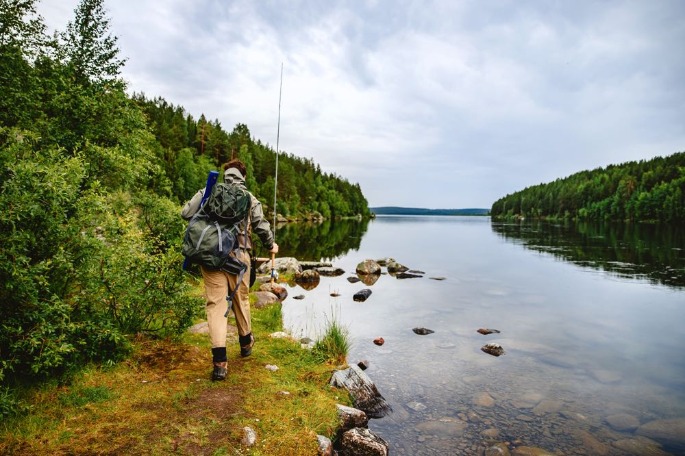 Man Fly Fishing a River Hiking with Backpack