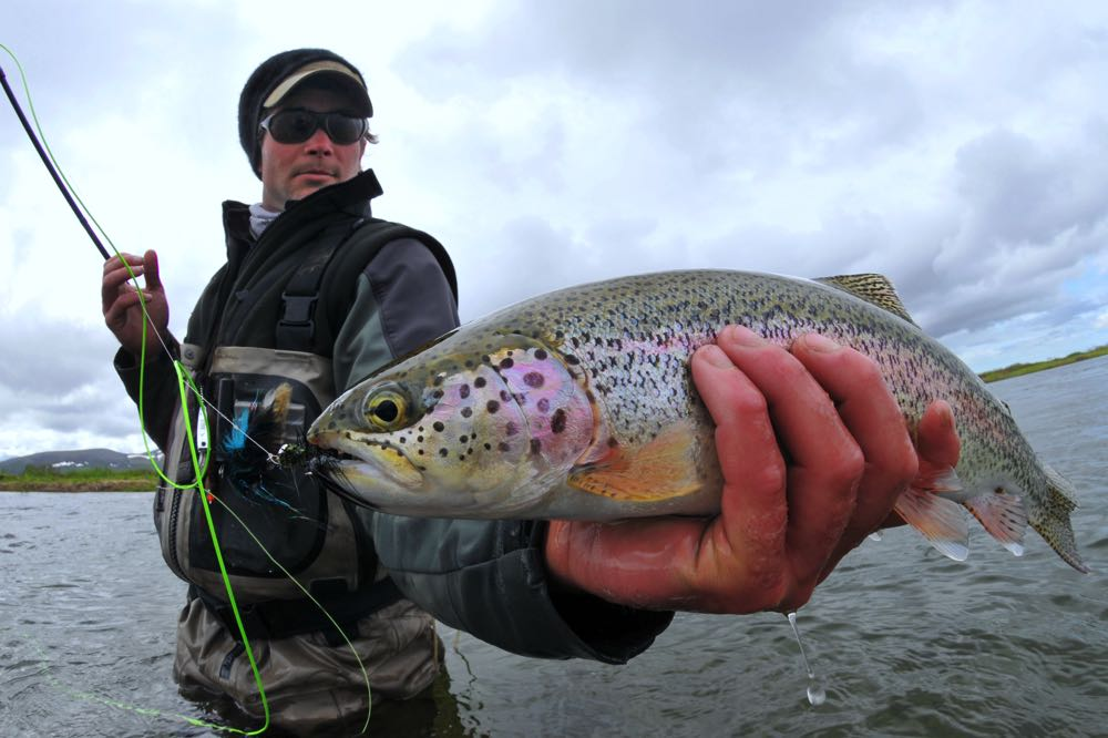 Man fly fishing holding a fish with good fly fishing sunglasses