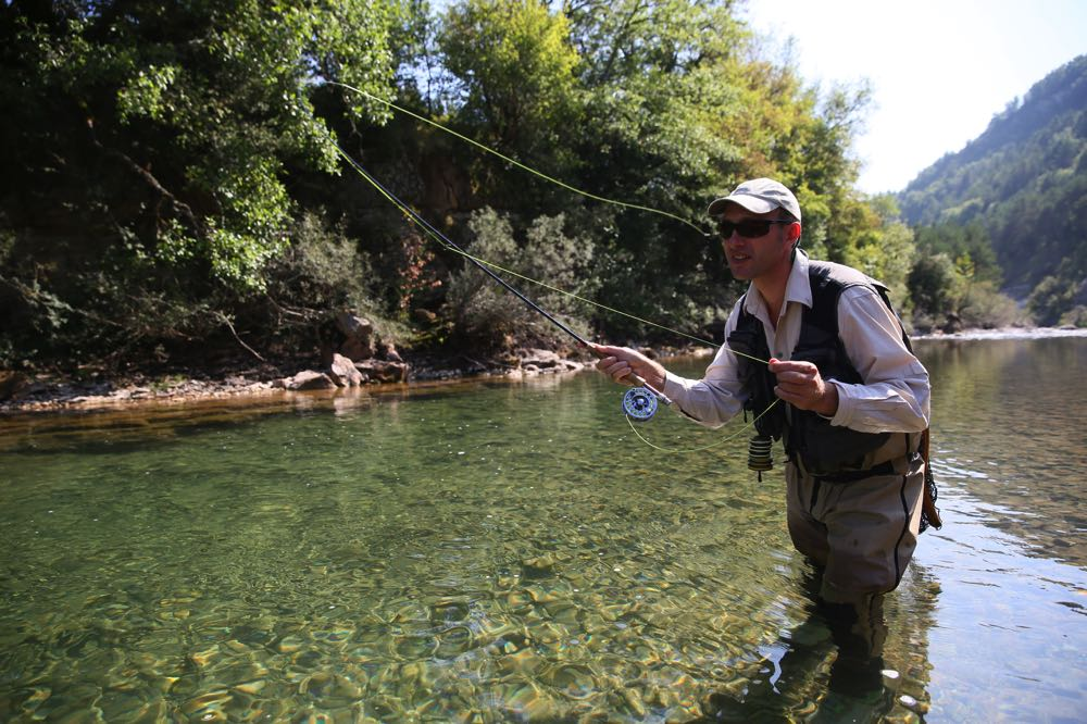 Man on river wading and fly fishing