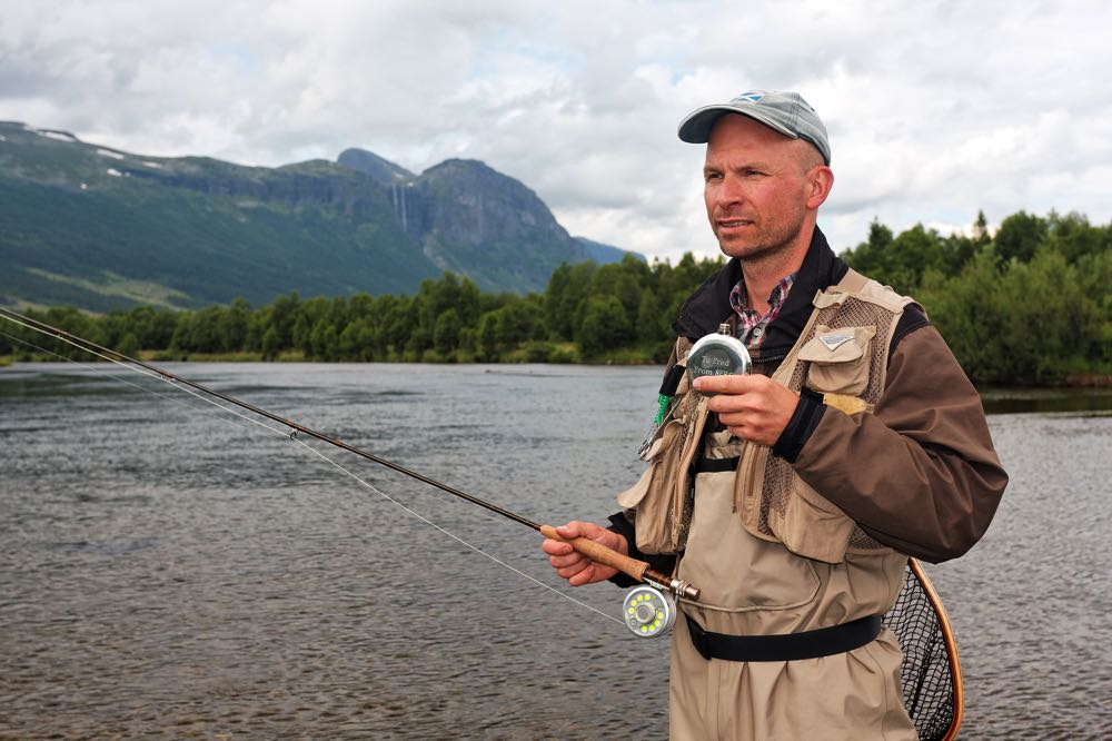 Man with fly fishing vest and 5 wt fly fishing rod on river