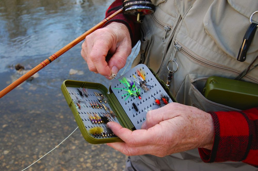 Opening fly box from pocket in fly fishing vest on river