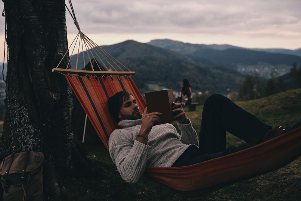 Man reading a fishing book while camping in hammock