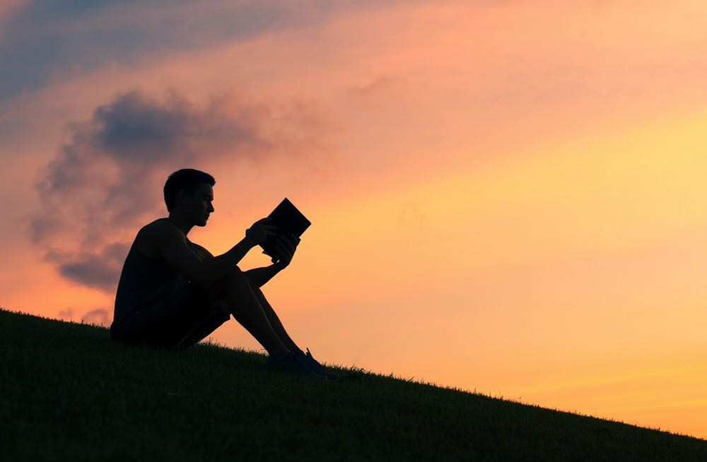Reading a fly fishing book on a hill at sunset