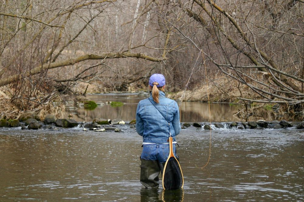 Woman fly fishing in Wisconsin on a river
