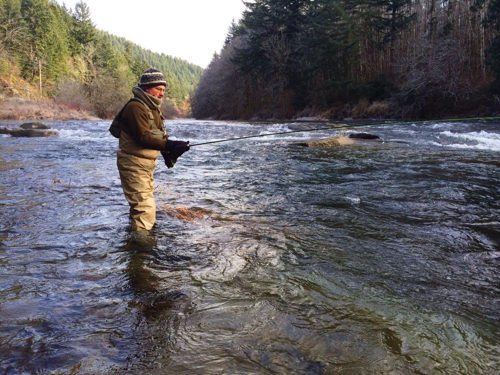 man fly fishing for steelhead in winter with gear on