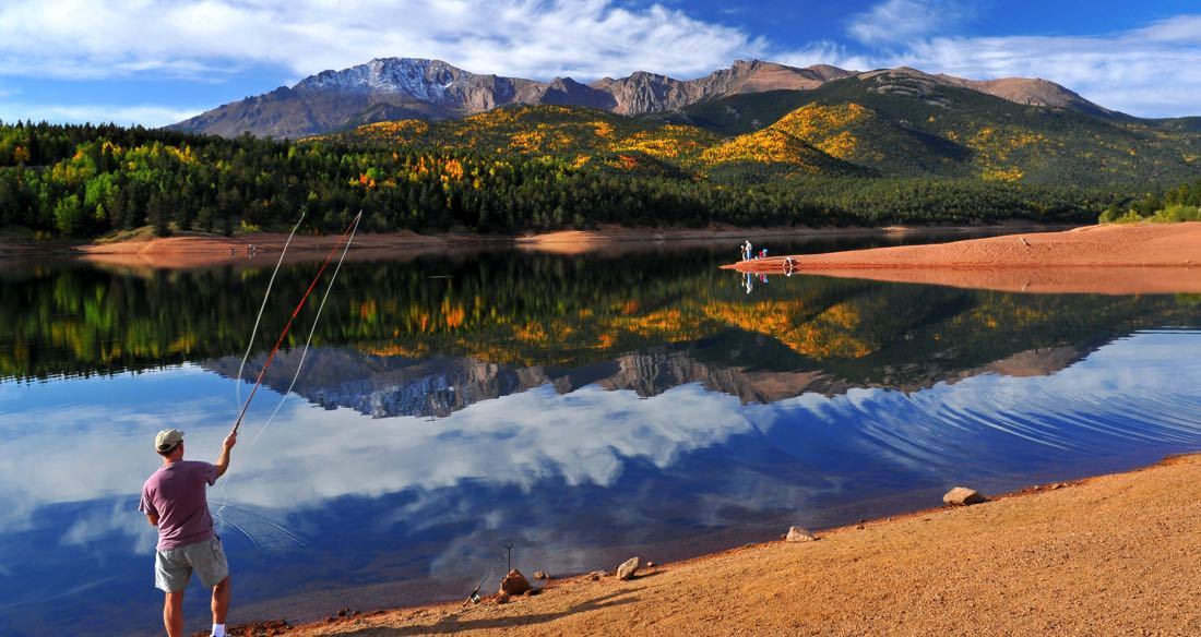 Man fly fishing on a glass calm reservoir in Colorado