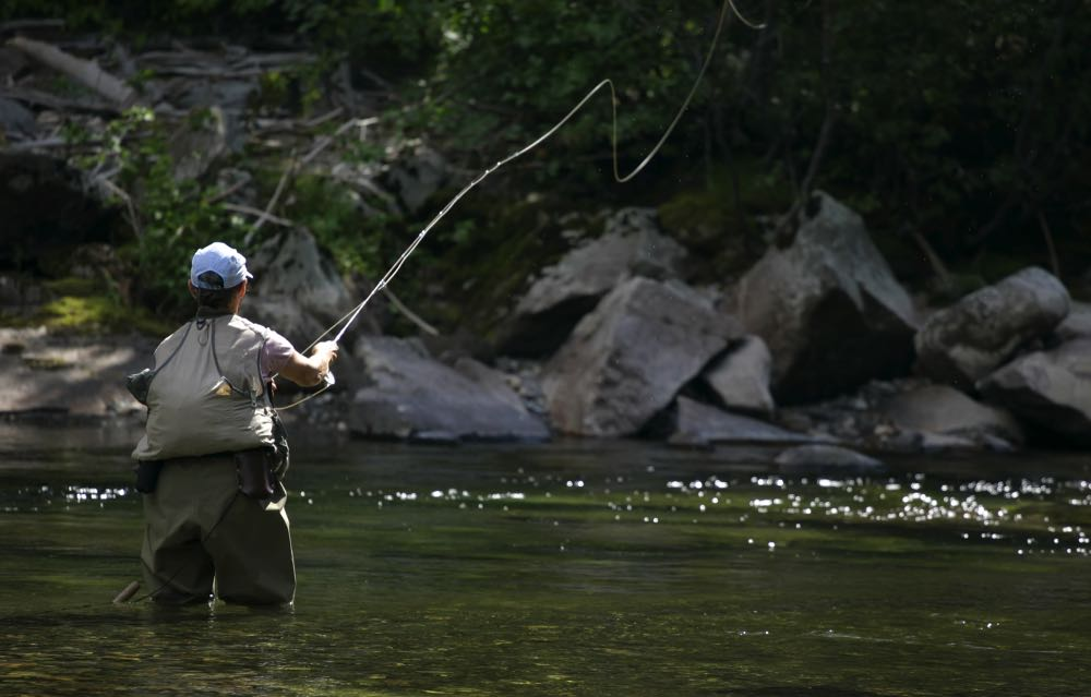 casting a fly rod fly fishing on a river