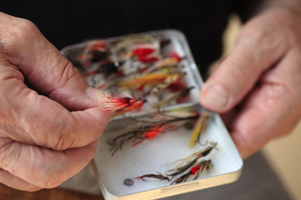 Man holds Best Bass Fly Fishing Flies above fly box