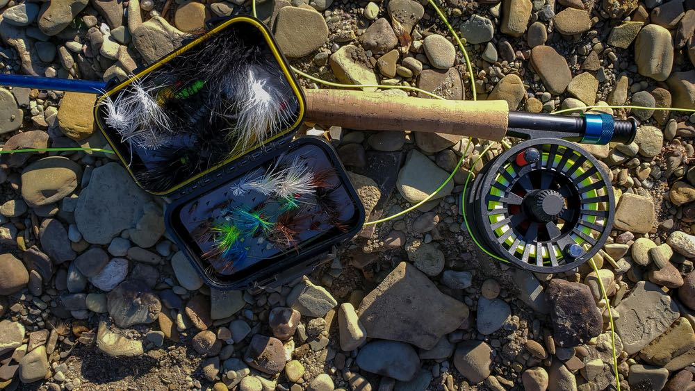 4 weight fly rod and reel with flies on river rocks