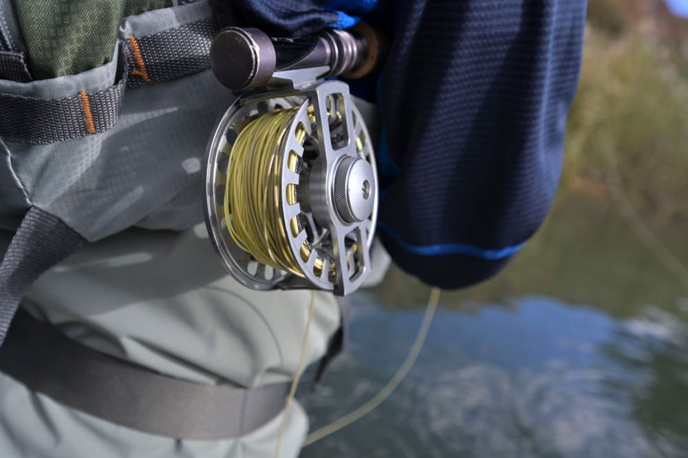 man holding an 8 weight fly reel under his arm