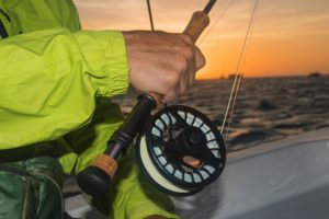guy on a boat holding a 10wt fly reel