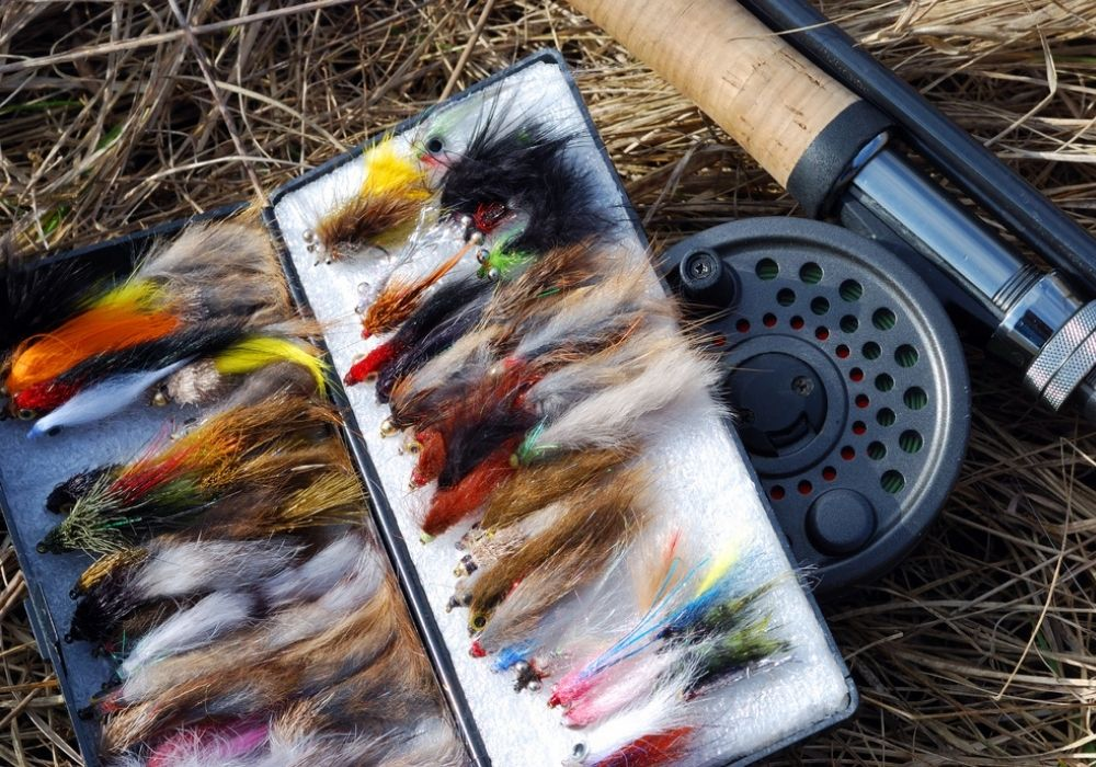 A collection of fly fishing flies and a fly fishing rod