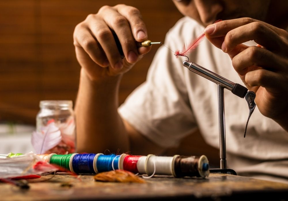 A close up on young man's hands tying a fly for fishing.