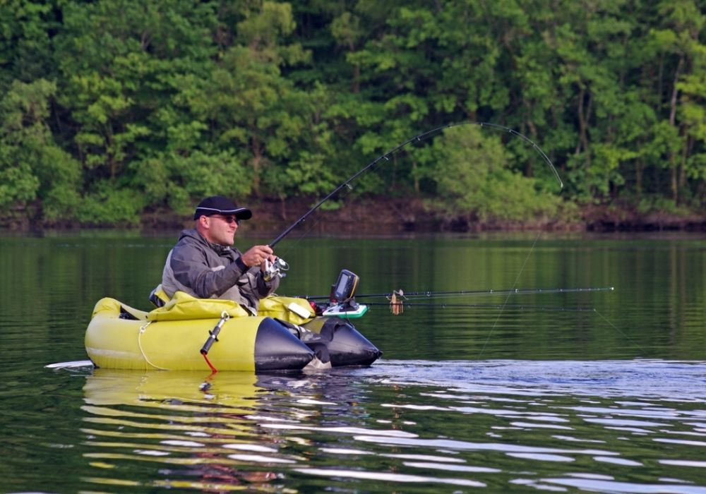 A fisherman fight against a pike. The man is sitting in the fishing inflatable boat. He also use a sonar fish finder to detect the fish underwater.