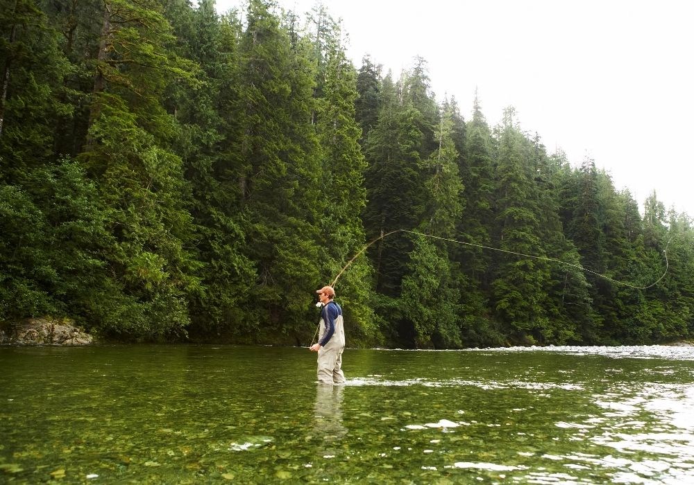 A fly angler wading through a river and fishing in a beautiful day.