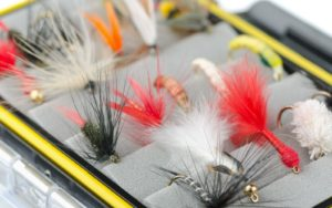 A set of wet flies for trout in a fly box