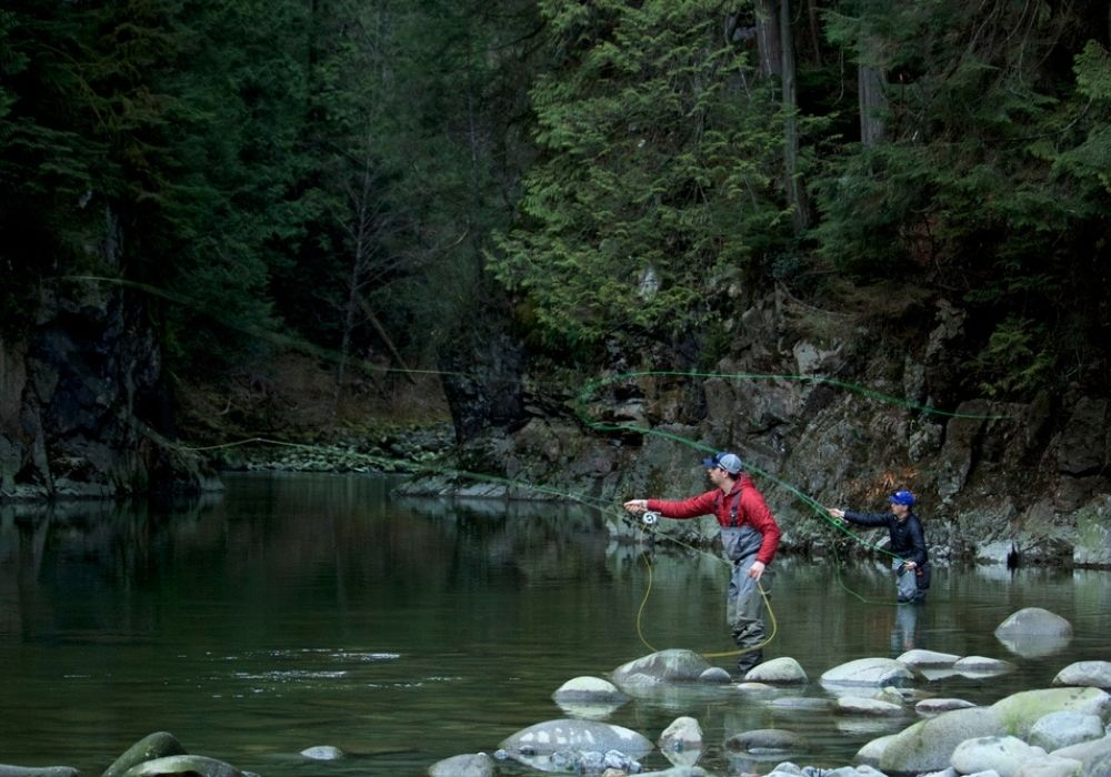 Two fly fisherman casting out their line in hopes to catch steelhead on the river