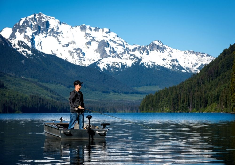 A fisherman fly fishing from a boat