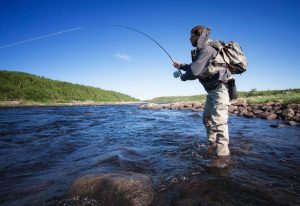 An angler fly fishing in the beautiful Maine