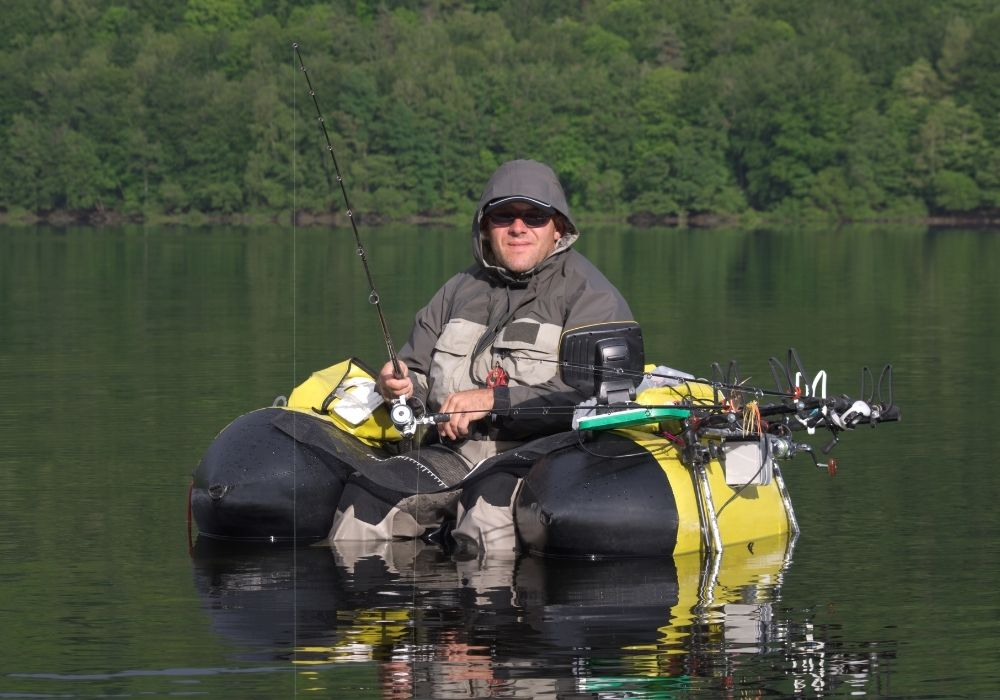 a fisherman fly fishing from a float tube with plenty of fly fishing gear