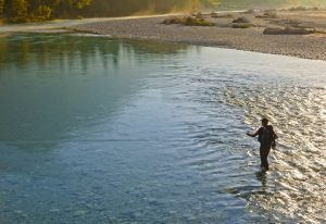 a man fly fishing on a river in Decorah