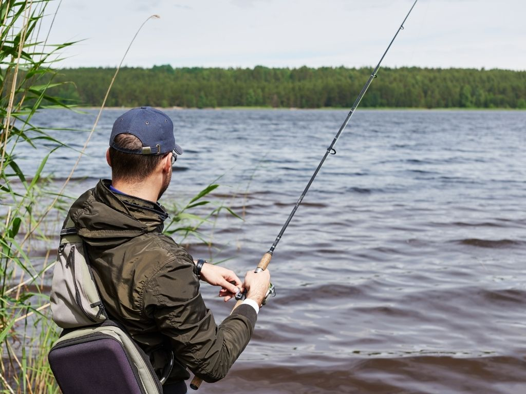 an angler casting a spinning rod on the river